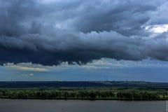 Durchlauf der dunklen Wolken über dem Fluss Stockbild