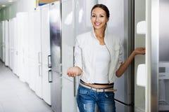 Durchschnittlicher weiblicher Kunde, der moderne Kühlschränke betrachtet Stockbilder