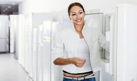 Durchschnittlicher weiblicher Kunde, der moderne Kühlschränke betrachtet Stockfotografie