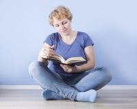 Durchschnittsalterfrau, die auf dem Boden und dem Ablesen sitzt Lizenzfreie Stockbilder