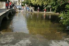 Durchschreiten des Flusses Windrush, Bourton auf dem Wasser Gloucestershire Großbritannien lizenzfreies stockfoto