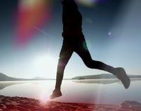 Durchsickern des Lichtes in der Linse Ausübung des Mannschattenbildes auf Strand gegen zu Morgen Sun Stockfotografie