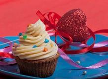 Durcissez avec de la crème crémeuse sur un plat bleu, décoré d'un ruban rouge et d'un coeur rouge Photos stock