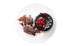 Durcissez avec des morceaux de chocolat foncé sur le plat blanc Photographie stock