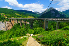 Durdevica Tara Bridge. BUDECEVICA, MONTENEGRO - JULY 02, 2015: Scene of the Durdevica Tara Bridge, across the Tara River Canyon, with locals and tourists, in Stock Image