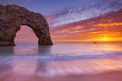 Durdle门岩石曲拱在日落的南英国 免版税库存图片