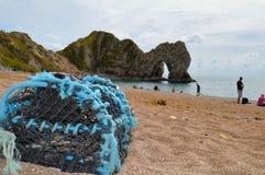 Durdle门看法在距离的与在前景的虾笼 免版税图库摄影
