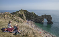 Durdle Door, Dorset - the meadows and people sunbathing. The picture shows Durdle Door, Dorset - the meadows and the blue waters. There are some people Royalty Free Stock Photography