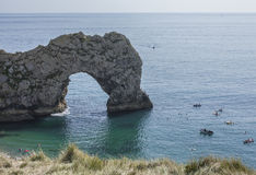Durdle Door limestone arch, England - blue waters and happy people. The picture shows Durdle Door - the natural limestone arch in Dorset, England Royalty Free Stock Photo