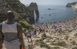Durdle Door - people on the beach and the blue waters. The picture shows some people walking towards the beach in Durdle Door, Dorset, England Royalty Free Stock Photo