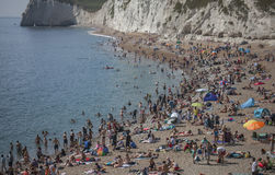 Durdle Door - people, beach, water, cliffs. The picture shows some people on the beach in Durdle Door, Dorset Stock Photo