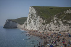 Durdle Door - people and the white cliffs. The picture shows some people on the beach and the white cliffs in the background in Durdle Door, Dorset, England Royalty Free Stock Photo