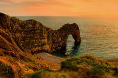 Durdle Door Sunset. Durdle Door, near Weymouth UK. a Natural Arch caused by limestone erosion.  A tent is pitched on the sand, however no human faces visible Stock Photos