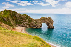 Durdle Door, travel attraction on South England, Dorset. In sunny summer day with calm azure sea and blue sky. View from top of cliffs royalty free stock image