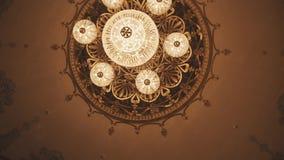 Dure gouden kroonluchter op concertzaalplafond met muurschilderingen stock videobeelden