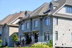 Dure moderne huizen in de stad met reusachtige vensters Stock Afbeeldingen
