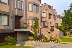 Dure moderne huizen in de stad met reusachtige vensters Stock Foto