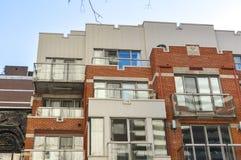 Dure oude en nieuwe huizen met reusachtige vensters Stock Afbeelding