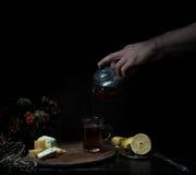 Durée toujours 1 Les mains masculines versent le thé dans la tasse transparente fond foncé, vintage Photos libres de droits