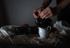 Durée toujours 1 Les mains masculines versent le thé dans la tasse transparente fond foncé, vintage Photos stock