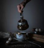 Durée toujours 1 les mains versent le thé dans la tasse transparente fond foncé, vintage Photographie stock