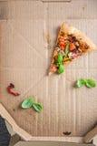 Durez une tranche de pizza végétarienne faite maison dans la boîte Images stock