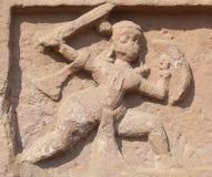 Durg, Chhattisgarh, Indien - Januari 18, 2009 forntida stenbaslättnad av en krigare med ett svärd och en sköld royaltyfri bild