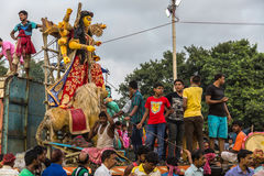 Durga idol being brought down from a truck by group of workers for immersion in the Ganges river. Stock Photo