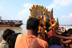 Durga puja festival. Devotees immerse huge decorated Durga idol in Hubli river during Durga Puja festival in Kolkata, India royalty free stock images