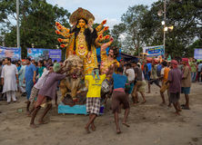 Durga puja workers push Durga idol to the Ganges river for immersion at Babughat Kolkata. Royalty Free Stock Photo