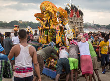 Durga puja - workers push Durga idol to the Ganges river for immersion at Babughat Kolkata. Royalty Free Stock Images
