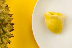 Durian σε ένα άσπρο πιάτο με τον πράσινο φλοιό ακίδων και το κίτρινο backgr Στοκ φωτογραφία με δικαίωμα ελεύθερης χρήσης