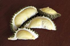 Durian peeled on the wooden table, four pieces. Durian is an oval spiny tropical fruit containing a creamy pulp. stock images