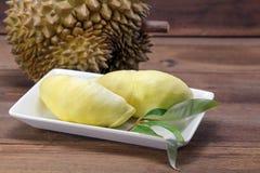Durian und Durian treiben auf weißem Teller, hölzerner Hintergrund Blätter lizenzfreie stockfotos