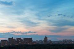 Durk blå och rosa natthimmel över den stads- gatan Arkivfoton