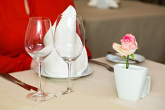 Durk in red is waiting at the restaurant. Table set service with silverware and glass stemware at restaurant before. Royalty Free Stock Photography