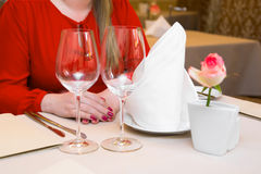 Durk in red is waiting at the restaurant. Table set service with silverware and glass stemware at restaurant before. Stock Photos