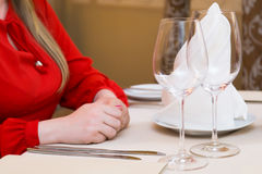 Durk in red is waiting at the restaurant. Table set service with silverware and glass stemware at restaurant before. Stock Image