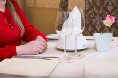 Durk in red is waiting at the restaurant. Table set service with silverware and glass stemware at restaurant before. Royalty Free Stock Images