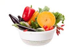 Durkslag med grönsaker på vit Arkivbilder
