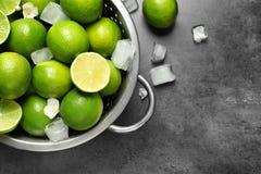 Durkslag med nya mogna limefrukter och iskuber Fotografering för Bildbyråer