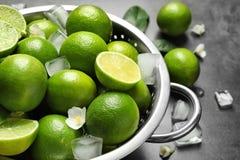 Durkslag med nya mogna limefrukter och iskuber Royaltyfri Foto