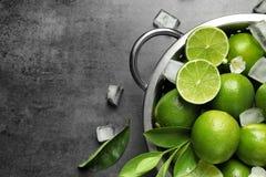 Durkslag med nya mogna limefrukter och iskuber Arkivfoton