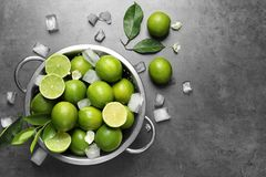 Durkslag med nya mogna limefrukter och iskuber Royaltyfri Fotografi