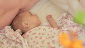 Durmiendo en el bebé de la arena, sobre quien el juguete-carrusel de giro del ` s de los niños almacen de video
