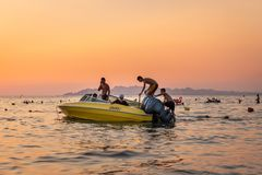 Orange and yellow sunset with people in a moored motorboat against the horizon. DURRES ALBANIA, AUGUST 5, 2018: Close sea view of orange and yellow sunset with stock photos
