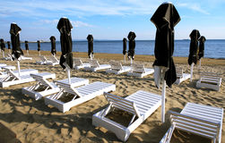 DURRES. Albania. Durres. Black sun umbrellas and white sun beds for relaxing on the Adriatic coast in a summer day Stock Image