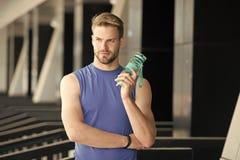 Durst und Gesundheit Sportlergriff-Wasserflasche auf Stadion Geeigneter Mann mit der Plastikflasche im Freien Aufenthalt hydratis lizenzfreie stockfotografie