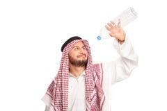 Durstiger Araber, der eine leere Plastikflasche hält Stockfotografie