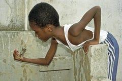 Durstiger brasilianischer Junge, der versucht, Wassertröpfchen zu fangen Stockfoto
